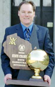 Rufus King Boy's Basketball coach Jim Gosz holding the team's second state championship trophy
